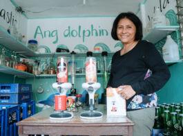 Nanay Lilian Gordoncillo em pé ao lado de dois dispensadores de café sobre uma mesa em uma sala cheia de engradados de bebidas (Usaid)