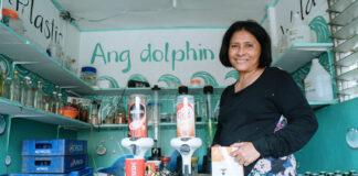 Nanay Lilian Gordoncillo debout à côté de deux distributeurs placés sur une table dans une salle remplie de caisses de boissons (USAID)