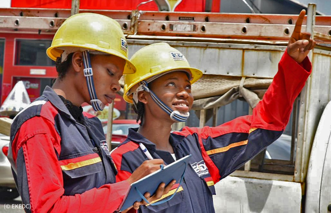 Two women in hard hats, one writing and one pointing skyward (© EKEDC)