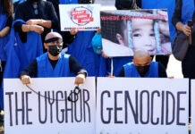 "Demonstrators wearing blue and holding signs including a large one that reads ""THE UYGHUR GENOCIDE"" (© Jacquelyn Martin/AP Images)"