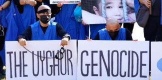 Personas con carteles que dicen 'genocidio uigur' (© Jacquelyn Martin/AP Images)