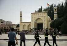 Civilians and police officers walking by a yellow mosque with two minarets (© David Liu/Getty Images)