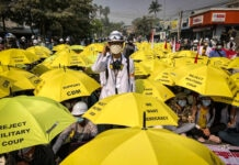 Man standing in middle of crowd of people sitting down with yellow umbrellas (© AP Images)