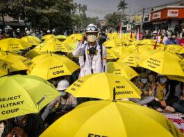 Homem de pé no meio de uma multidão de pessoas sentadas segurando guarda-chuvas amarelos (© AP Images)