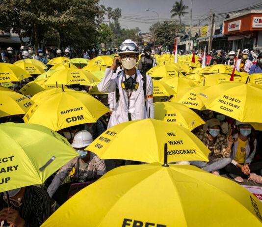 مجمعے کے درمیان کھڑا ایک آدمی اور اس کے ارد گرد لوگ پیلے رنگ کی چھتریوں کے نیچے بیٹھے ہوئے ہیں۔ (© AP Images)