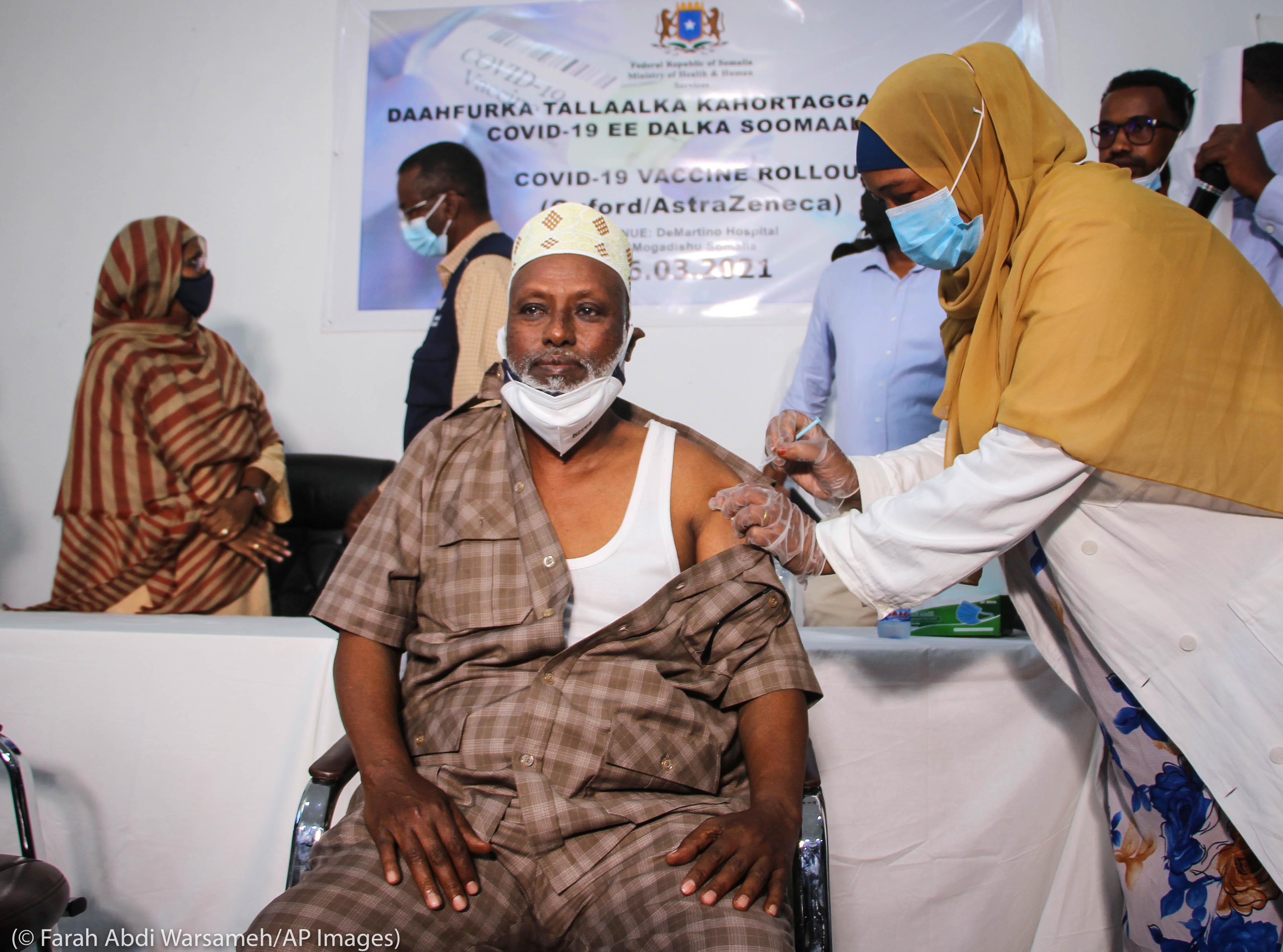 Un anciano somalí es vacunado mientras otros observan cerca (© Farah Abdi Warsameh/AP Images)