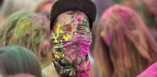 Person wearing ball cap and face covering coated in brightly colored powder, standing in crowd of people (© Daniel Knighton/Getty Images)