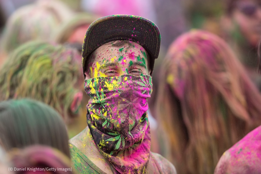 Person wearing ball cap and a face covering coated in brightly colored powder, standing in a crowd of people (© Daniel Knighton/Getty Images)