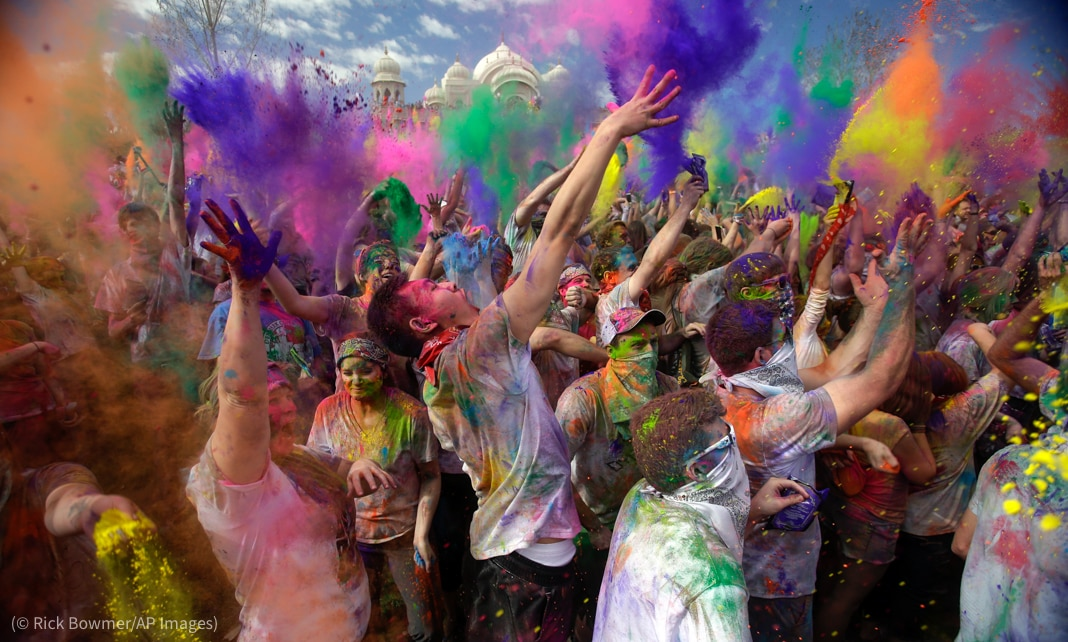 Revelers in crowd tossing brightly colored dust into the air (© Rick Bowmer/AP Images)