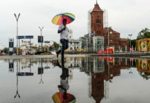 Buildings and person with umbrella reflected in water (© Arun Sankar/AFP/Getty Images)