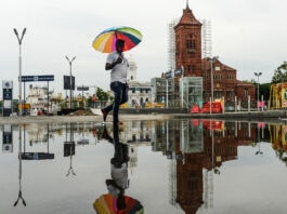Buildings and person with umbrella reflected in water