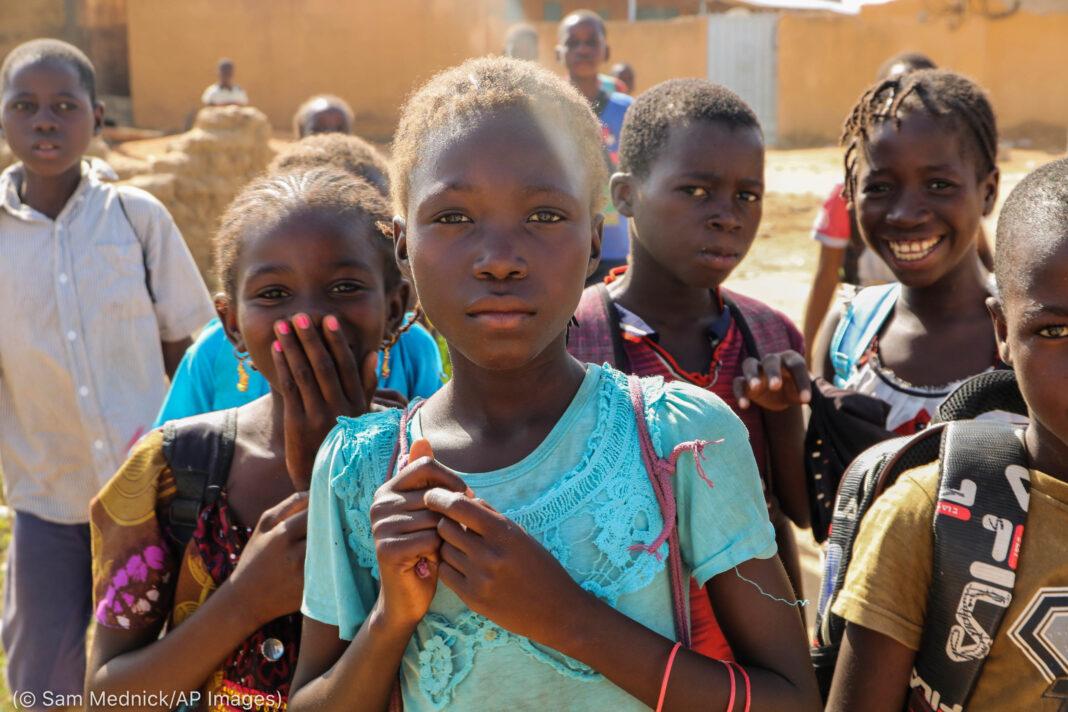 بچے کیمرے کی طرف دیکھ رہے ہیں۔ (© Sam Mednick/AP Images)