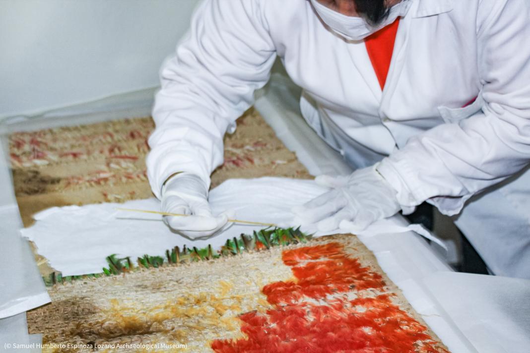 Une personne portant des vêtements de protection en train de réparer un textile (© Samuel Humberto Espinoza Lozano Archaeological Museum)