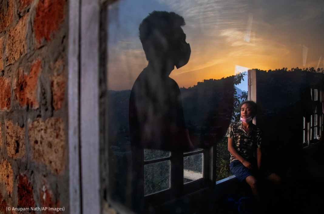 Woman seen through glass sitting on window sill, with reflected silhouette of man looking into sunset (© Anupam Nath/AP Images)