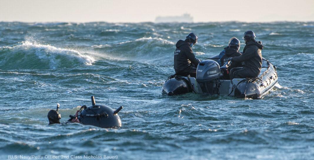 Hombre con una mina en el agua trabaja con hombres en una embarcación (U.S. Navy/suboficial de 2 ª clase Nicholas Bauer)