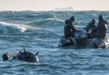 Man with mine in water working with men in boat (U.S. Navy/Petty Officer 2nd Class Nicholas Bauer)