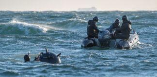 Homem com mina dentro d'água trabalhando perto de homens em barco inflável (Marinha dos EUA/Segundo-sargento Nicholas Bauer)