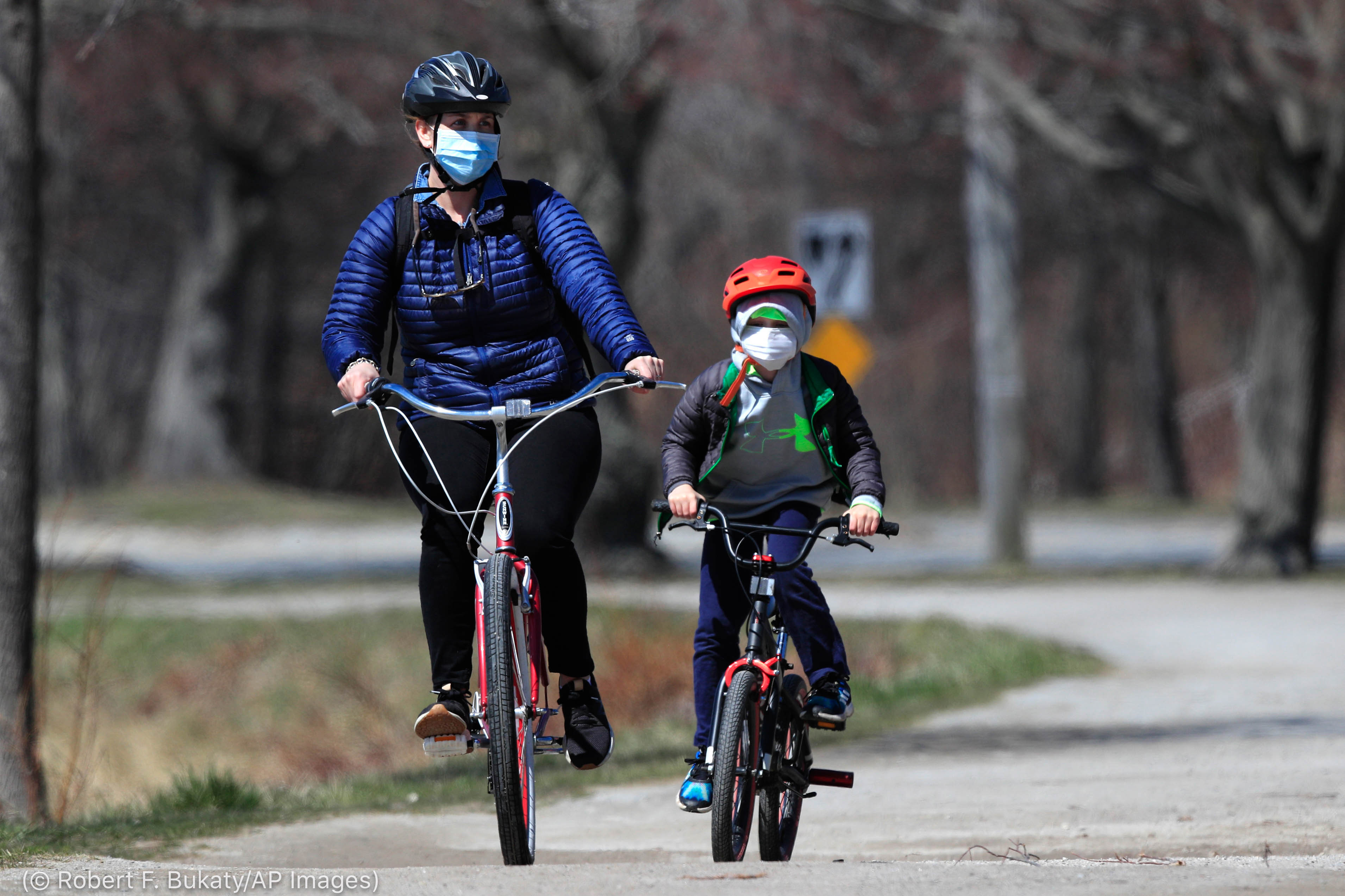 Adult and child wearing face masks while riding bicycles (© Robert F. Bukaty/AP Images)