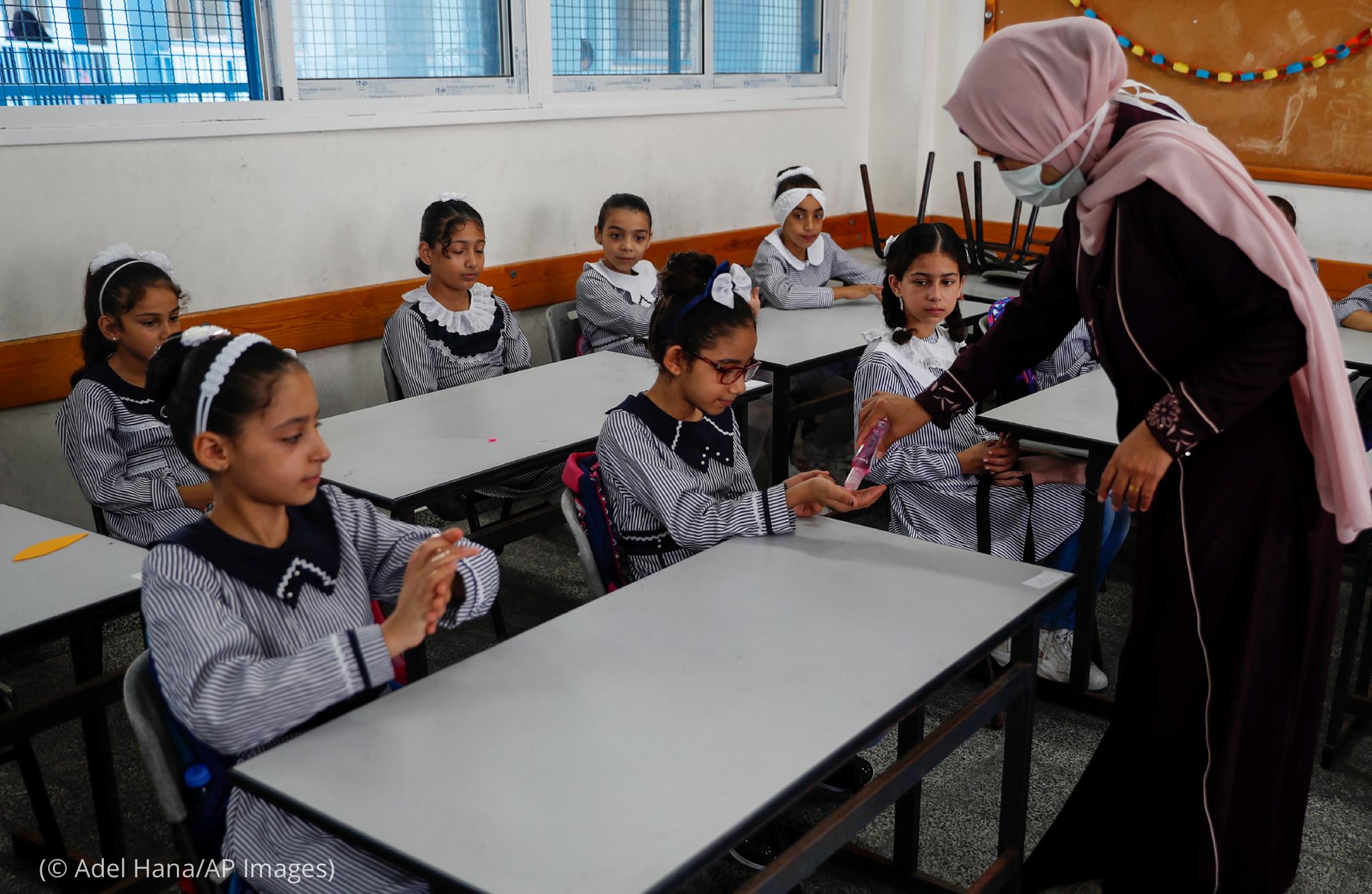 Una mujer vierte desinfectante de manos en la mano de un estudiante mientras otros estudiantes se sientan a las mesas y observan (© Adel Hana/AP Images)