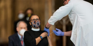 Woman wearing clerical collar receiving injection in arm (© Manuel Balce Ceneta/AP Images)