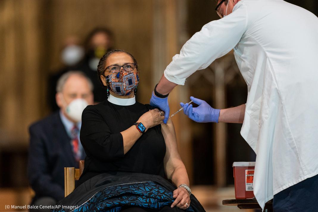Wanita dengan jubah keagamaan menerima suntikan di lengan (© Manuel Balce Ceneta/AP Images)