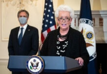Gayle Smith standing at lectern with Antony Blinken standing behind (© Al Drago/AP Images)