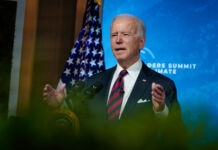 Joe Biden at lectern, speaking and gesturing (© Evan Vucci/AP Images)