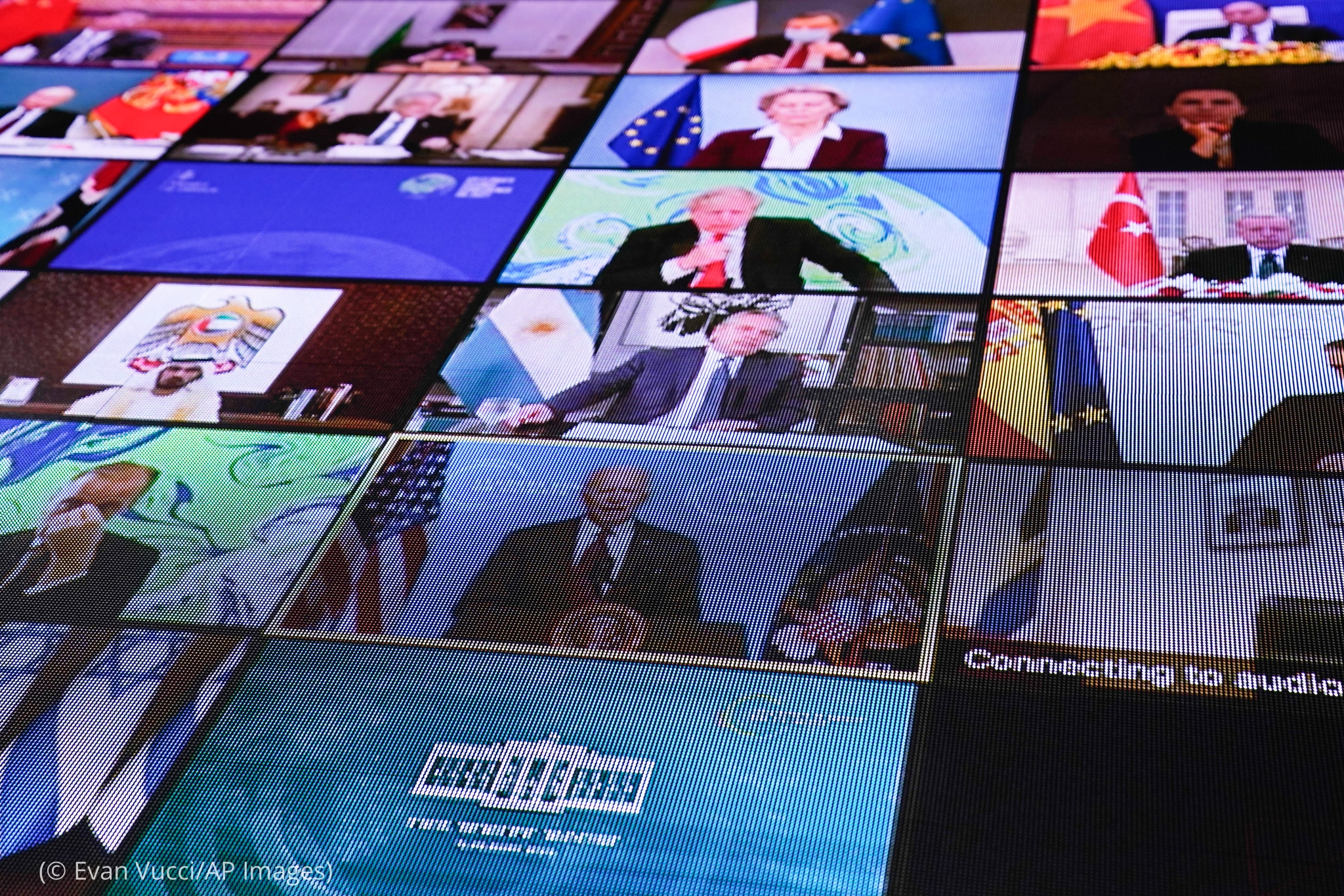 Computer screen showing multiple screens of world leaders attending meeting (© Evan Vucci/AP Images)
