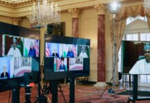 Três telões dispostos em um salão elegante; em dois deles aparecem telas menores exibindo a participação de líderes em reunião virtual (© Leah Millis/AP Images)