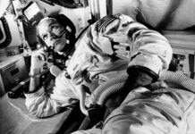 Astronaut leaning on one arm while wearing space suit (© AP Images)