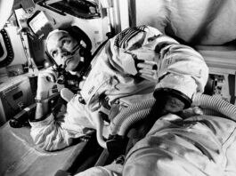 خلائی سوٹ پہنے ایک خلاباز بازو سے ٹیک لگائے بیٹھا ہے (© AP Images)