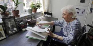 2015年,纽约的一位百岁艺术家在她的工作室里翻看自己的作品。(美联社图片)