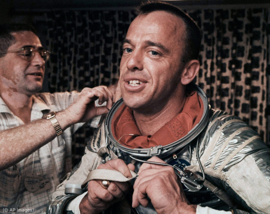 Man helping astronaut get out of his spacesuit (© AP Images)