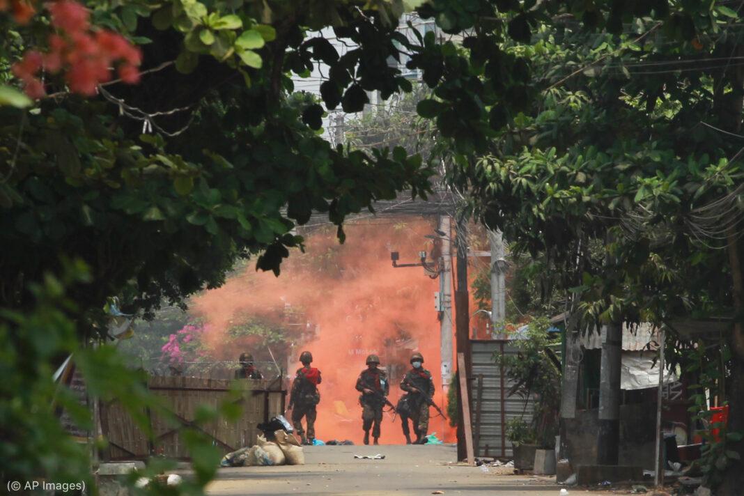 Soldados vistos à distância com fumaça avermelhada atrás deles em local com árvores e plantas (© AP Images)