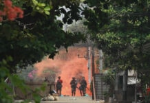 Soldiers in distance with reddish smoke behind them in an area with trees and plants (© AP Images)