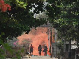 Tentara di kejauhan dengan latar belakang asap kemerahan di area dengan pepohonan dan tumbuhan (© AP Images)