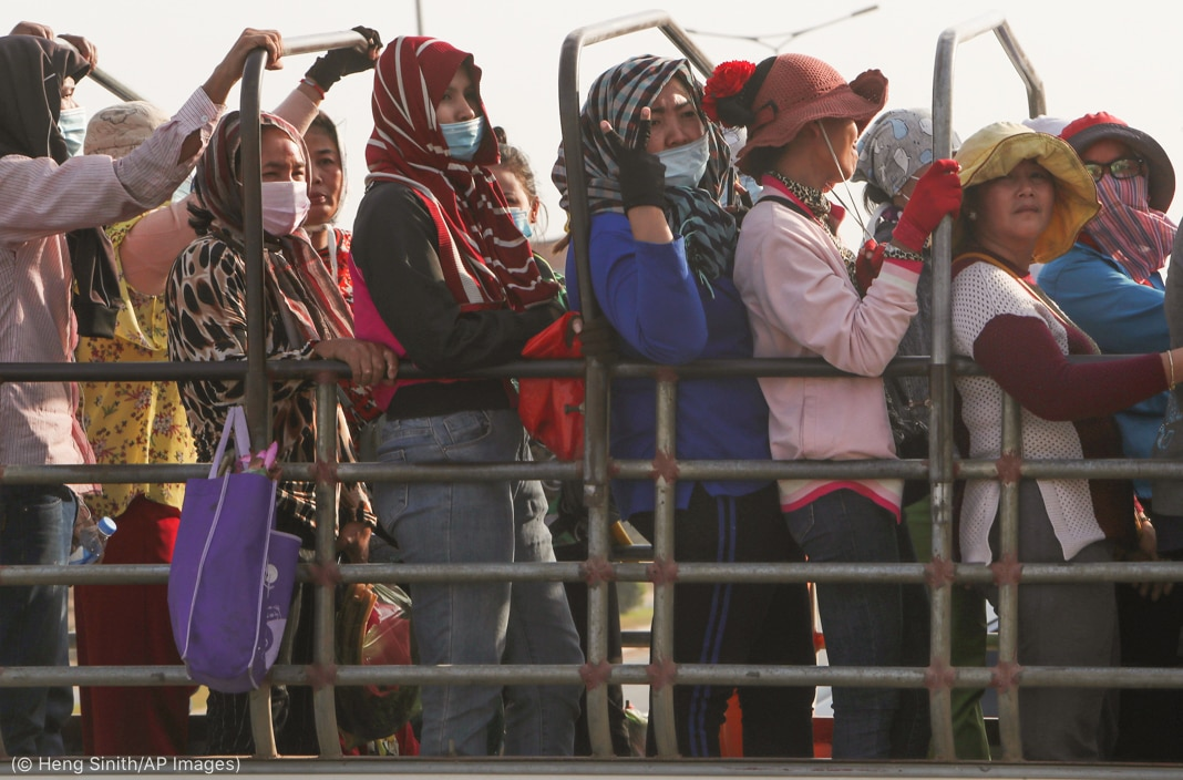 Workers standing in back of truck, holding on to metal bars (© Heng Sinith/AP Images)