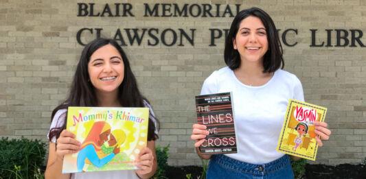 Две девочки с книгами в руках, стоящие перед библиотекой (Courtesy of Deyar Nasiri)