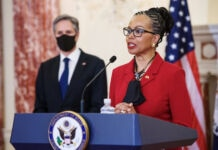 Former Ambassador Gina Abercrombie-Winstanley speaking on podium with Secretary of State Antony Blinken in the background (© Mandel Ngan/AP Images)