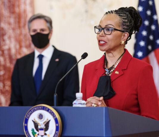 Former Ambassador Gina Abercrombie-Winstanley speaking on podium with Secretary of State Antony Blinken in the background (© Mandel Ngan/AP Images)