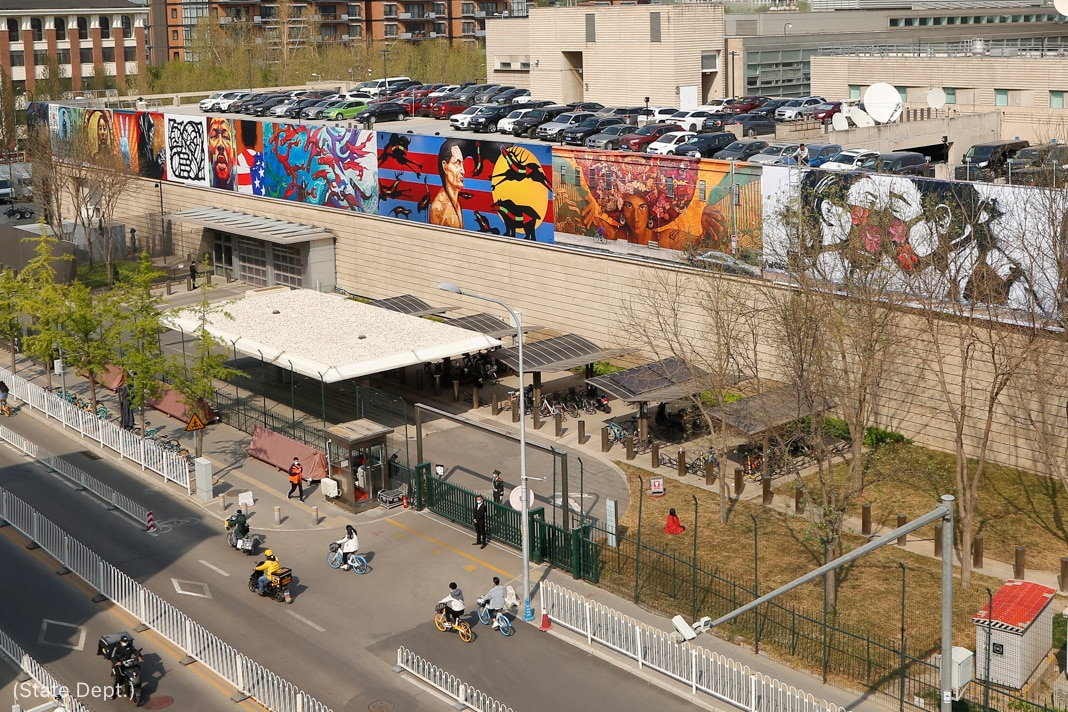 People in street biking past murals on embassy walls (State Dept.)