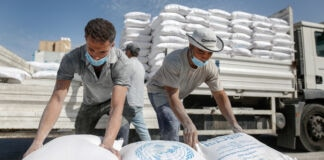 Men unloading bags from truck (© Sameh Rahmi/NurPhoto/Getty Images)