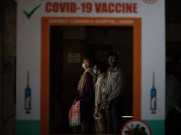 Personas esperando en una fila vista a través de un cartel de la vacuna contra COVID-19 (© Altaf Qadri/AP Images)