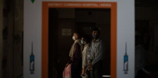 People waiting in line seen through a COVID-19 vaccine sign (© Altaf Qadri/AP Images)