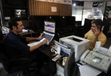 Two men sitting in internet cafe, one working on laptop, the other talking on cellphone (© Vahid Salemi/AP Images)