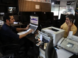 Two men at an Internet cafe, one working on a laptop, the other talking on a cell phone (© Vahid Salemi/AP Images)