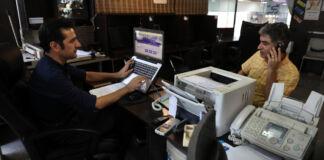 Dua pria duduk di kafe internet, yang satu bekerja dengan laptop, yang lain berbicara di ponsel (© Vahid Salemi/AP Images)