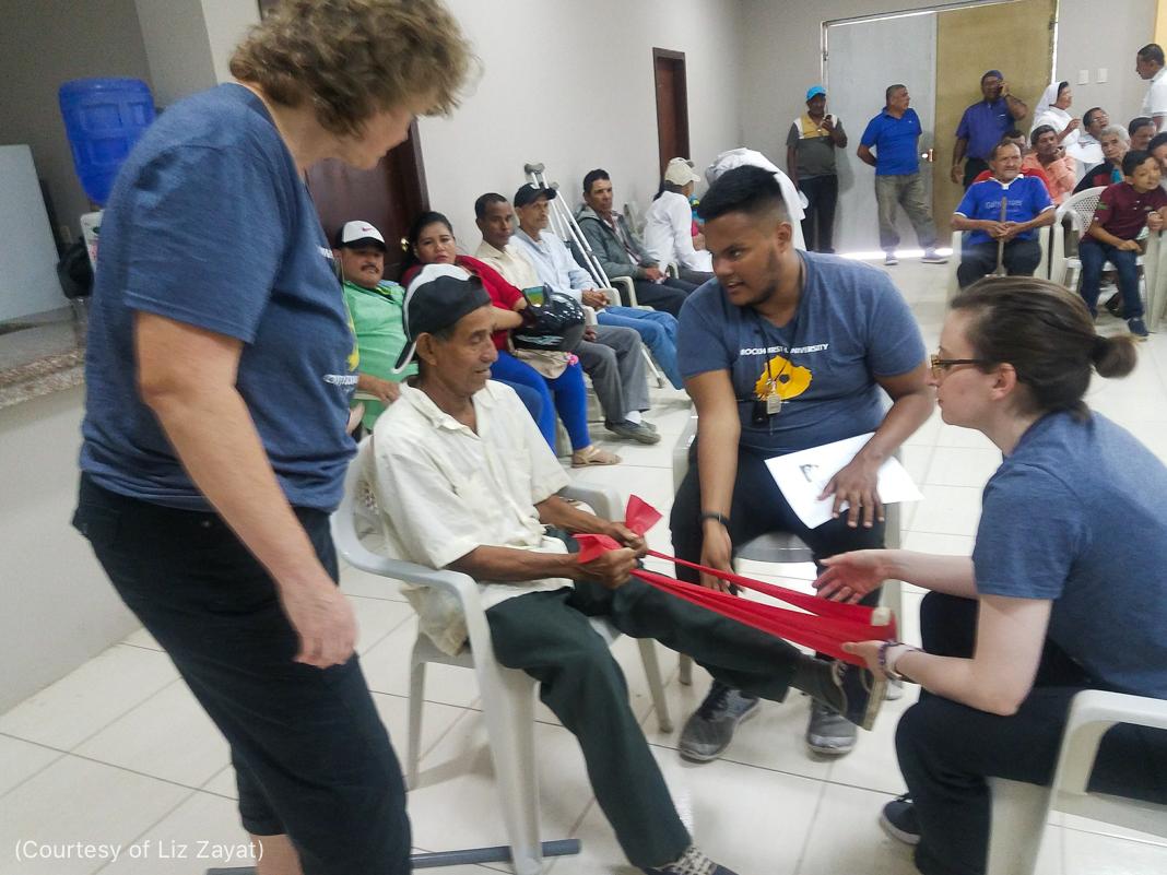 رجل يتحدث في حين تقوم امرأة بفحص ساق مريض بينما ينتظر مرضى آخرون (Courtesy of Liz Zayat)