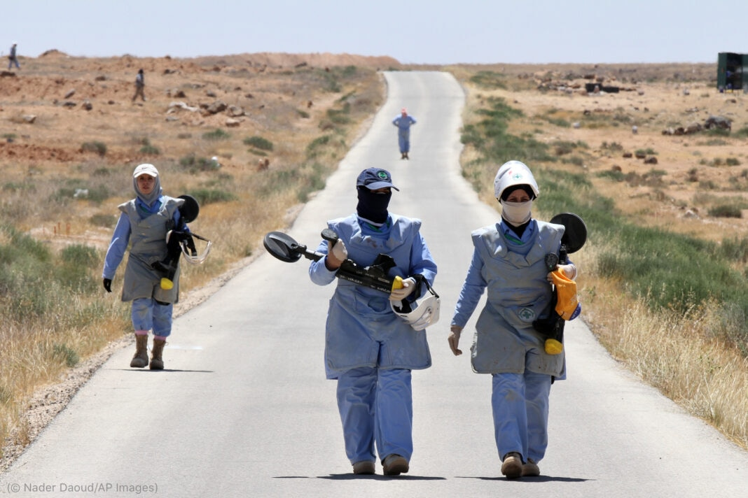 Women wearing blue personal protective equipment and carrying metal detectors (© Nader Daoud/AP Images)