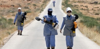 Women wearing personal protective equipment and carrying metal detectors walk down road (© Nader Daoud/AP Images)